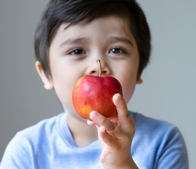Fronte confusa del ragazzo sveglio che tiene mela rossa organica sulla sua mano e che esamina macchina fotografica