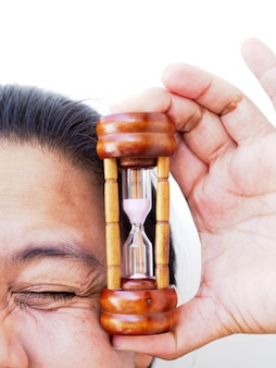 Fronte del primo piano della donna asiatica con la clessidra della tenuta della mano, tempo di prendersi cura di pelle e rughe.