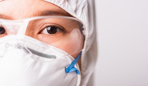 Fronte del primo piano di medico della donna in uniforme ppe che indossa la maschera di protezione n95 protettivo e gli occhiali in laboratorio