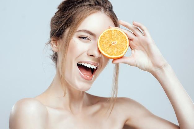 Fronte di bella donna con arancia succosa