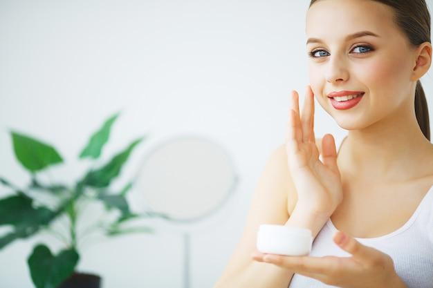 Fronte di bellezza della donna con crema cosmetica sul viso