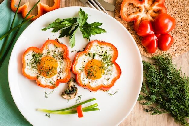 Fronte divertente fatto di uova fritte, peperoni, cipolle e funghi su un piatto