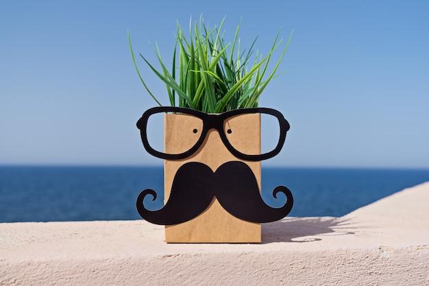 Fronte divertente sul sacco di carta con i baffi e gli occhiali su cielo blu