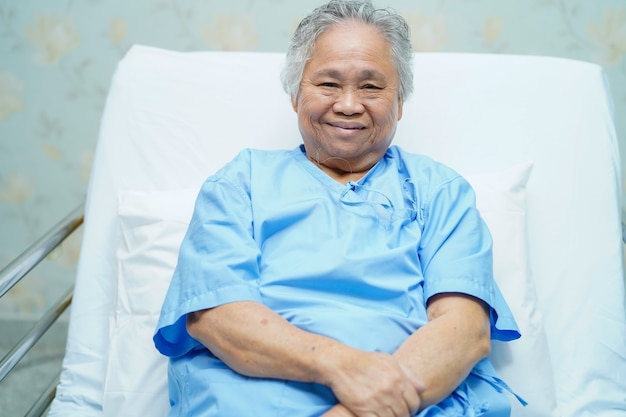 Fronte luminoso di sorriso paziente asiatico senior della donna mentre sedendosi sul letto in ospedale.