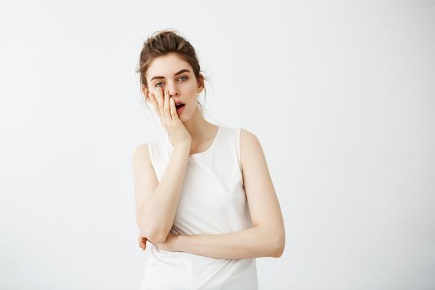Fronte nascondentesi della giovane donna graziosa stanca annoiata dietro la mano