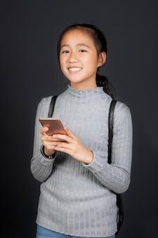 Fronte sorridente a trentadue denti del ritratto dell'adolescente asiatico con lo smart phone a disposizione
