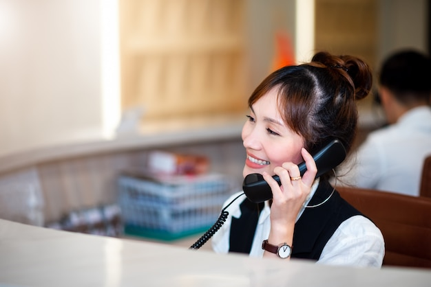 Fronte sorridente della donna asiatica professionale astuta in operatore, dipartimento della call center. telefono che lavora con happy service mind dipartimento di telecomunicazioni