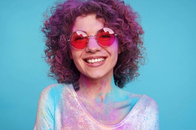 Fronte sorridente della giovane donna coperto di polvere variopinta di holi sopra fondo blu