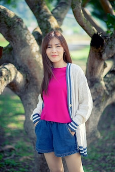 Fronte sorridente toothy di bella donna più giovane asiatica in piedi nel parco