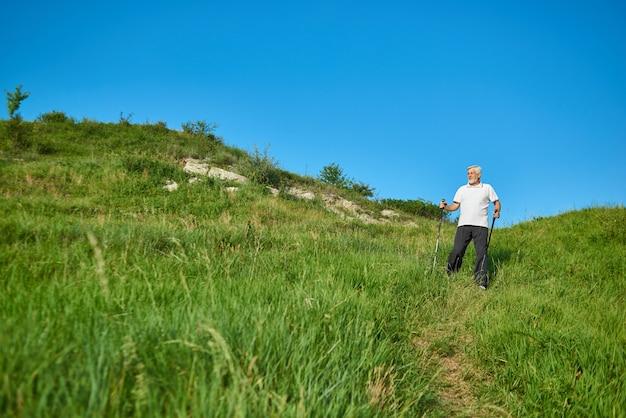 Frontview dell'uomo anziano che cammina sul campo verde con i bastoni di inseguimento.