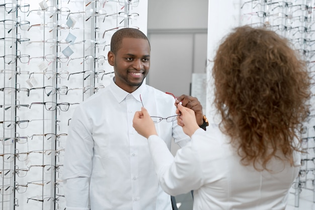Frontview dell'uomo sorridente che prova sugli occhiali in negozio ottico.