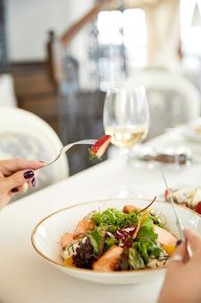 Frontview di un'insalata fresca in primo piano e un bicchiere con un vino bianco