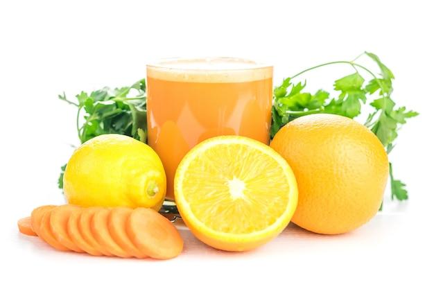 Frullati di carote con arancia e limone su un tavolo di legno bianco.