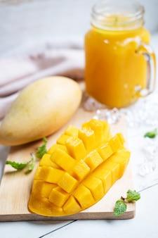 Frullati di mango rinfrescanti in vetro con mango maturo sul tavolo di legno bianco