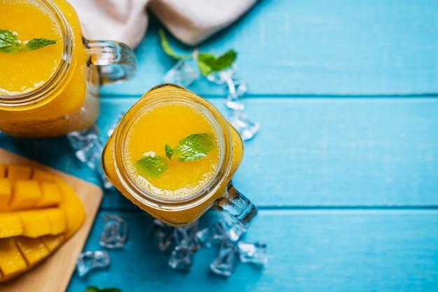 Frullati di rinfresco del mango in vetro con il mango maturo sulla tavola e sul copyspace di legno, vista superiore