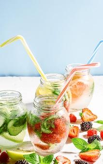 Frullati disintossicanti di frutta e verdura fresca in vasetti di vetro con tubi