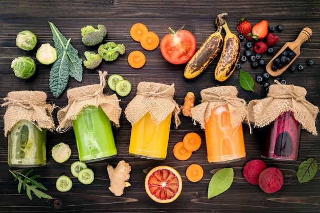 Frullati e succhi sani variopinti in bottiglie con frutta tropicale e superfoods freschi su fondo di legno.