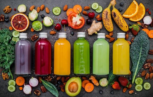 Frullati e succhi sani variopinti in bottiglie con frutta tropicale e superfoods freschi su fondo di pietra scuro con lo spazio della copia.