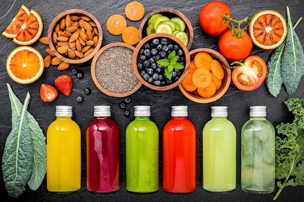 Frullati e succhi sani variopinti in bottiglie con frutta tropicale fresca su fondo di pietra scuro.