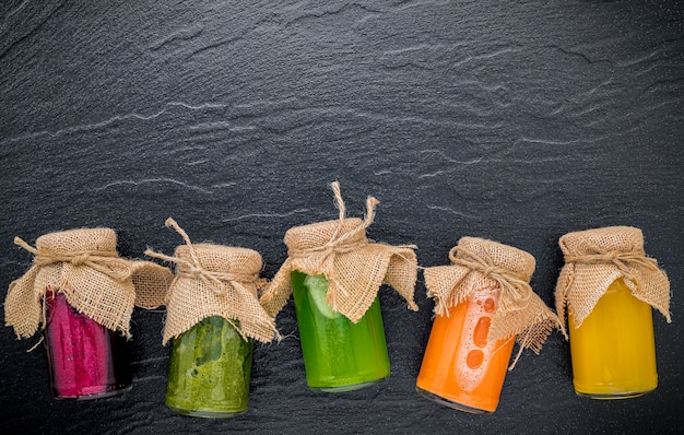 Frullati e succhi sani variopinti in bottiglie su fondo di pietra scuro con lo spazio della copia.
