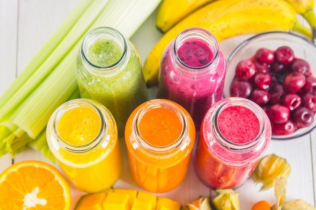 Frullati multicolori in bottiglie di mango, arancia, banana, sedano, frutti di bosco, su un tavolo di legno.