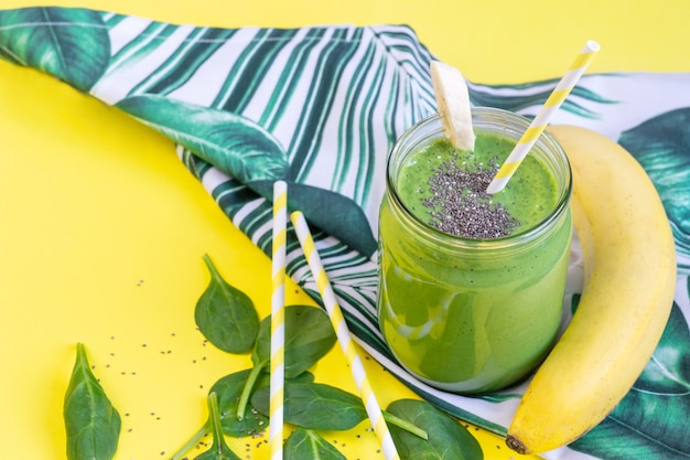 Frullati verdi degli spinaci in barattolo con i semi di chia, concetto sano dell'alimento, prima colazione, fondo giallo
