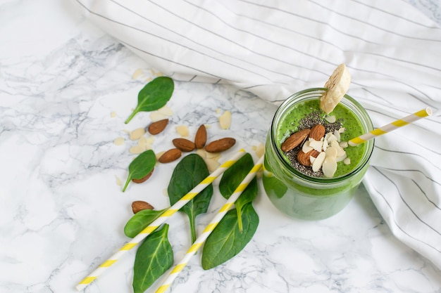 Frullati verdi degli spinaci in barattolo con i semi di chia, mandorle matte, concetto sano dell'alimento