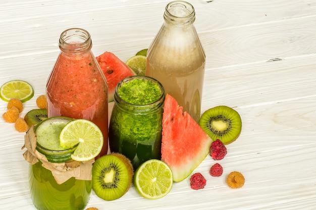 Frullati verdi e rossi in un barattolo con lime