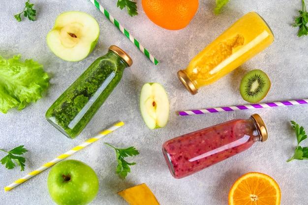Frullati verdi, gialli, viola in bottiglie di ribes, prezzemolo, mela, kiwi, arancia su un tavolo grigio.