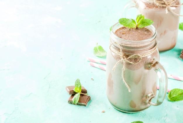 Frullato al cioccolato o frappè con menta e paglia, in barattolo di vetro su sfondo azzurro,