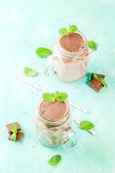 Frullato al cioccolato o frappè con menta e paglia in barattolo di vetro su sfondo azzurro
