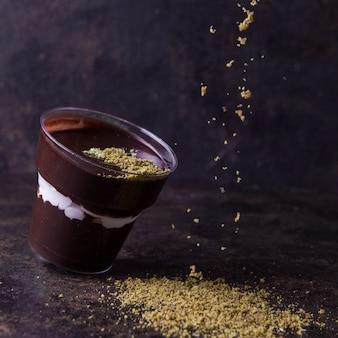 Frullato al cioccolato vista laterale con briciole di noci in bicchiere di plastica