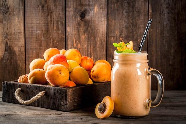 Frullato biologico fatto in casa da yogurt e albicocca. in mason jar, su un vecchio tavolo di legno rustico, con albicocche e foglie di menta. copia spazio