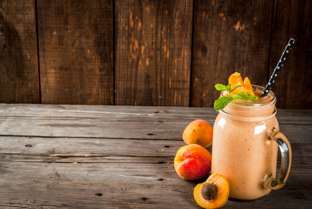 Frullato biologico fatto in casa da yogurt e albicocca. in mason jar, su un vecchio tavolo di legno rustico
