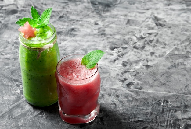Frullato cocktail tropicale con menta, fette di anguria e cubetti di ghiaccio su una superficie di cemento grigia