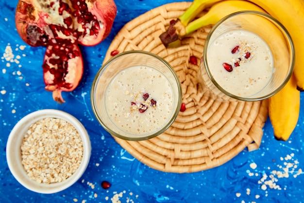Frullato con avena o farina d'avena, banana e melograno su blu.
