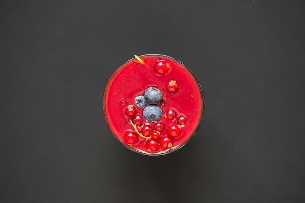 Frullato con frutti di bosco in un bicchiere su sfondo nero