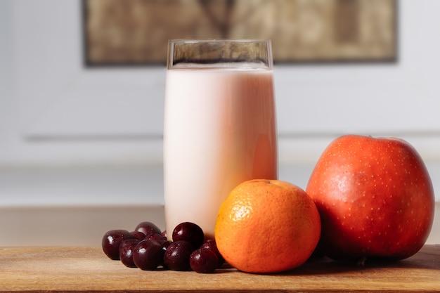 Frullato di agrumi ciliegia ciliegia su una tavola di legno con frutti davanti a una finestra