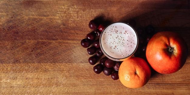 Frullato di agrumi ciliegia ciliegia su una tavola di legno con frutti su una superficie nera