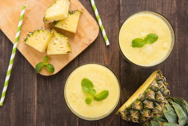 Frullato di ananas con ananas fresco sul tavolo di legno