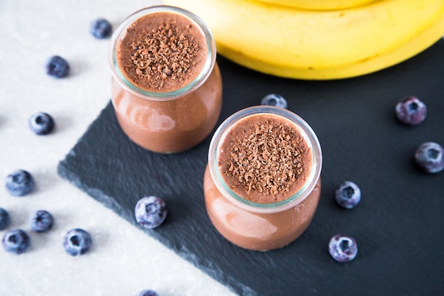 Frullato di banana al cioccolato con semi di chia e mirtillo su uno sfondo di ardesia e pietra.