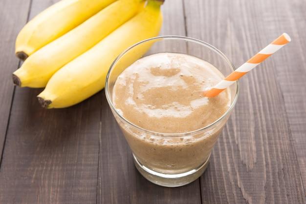 Frullato di banana e banana fresca sulla tavola di legno