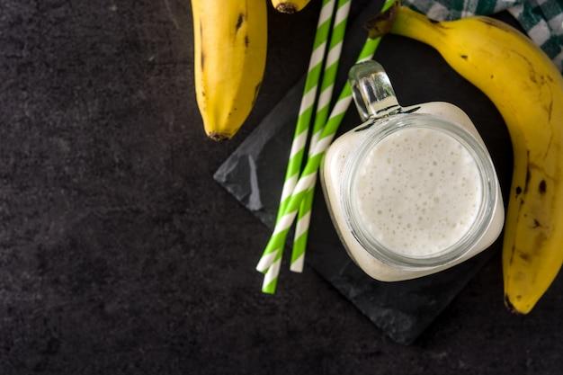 Frullato di banana in barattolo sulla vista nera e superiore