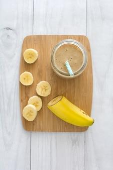Frullato di banana su una vista del piano del tavolo in legno bianco