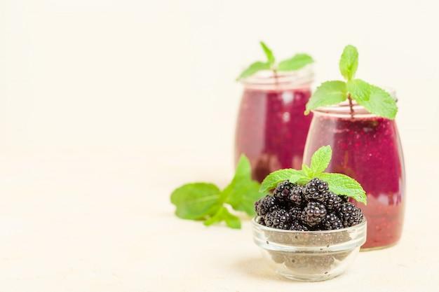 Frullato di blackberry - bevanda cruda biologica con bacche fresche foresta matura su sfondo giallo pastello.
