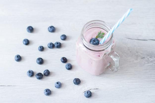 Frullato di blueberrie in una tazza di vaso con una cannuccia sul tavolo