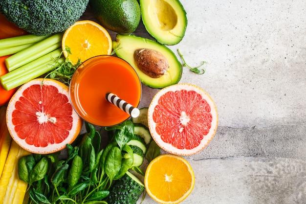 Frullato di disintossicazione arancione in vetro. ingredienti per lo sfondo di frullato di disintossicazione, vista dall'alto. concetto di cibo sano.