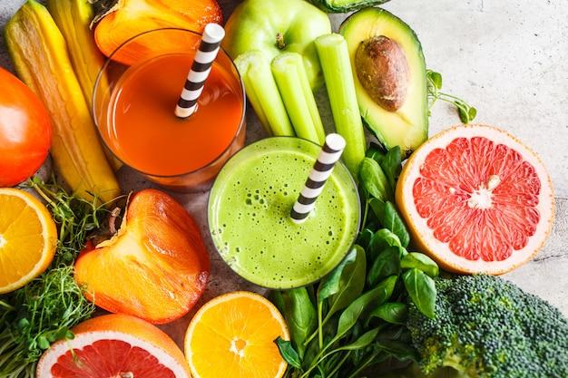 Frullato di disintossicazione verde e arancione in vetro. ingredienti per lo sfondo di frullato di disintossicazione. concetto di cibo sano.