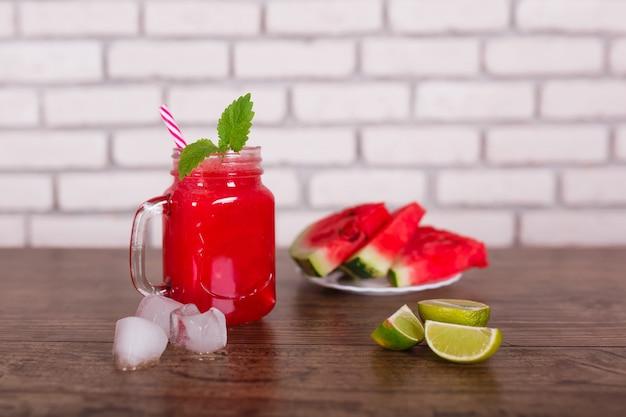 Frullato di frutta rossa mescolato in barattolo di vetro con paglia, pezzi di ghiaccio. fette di anguria sul piatto. messa a fuoco selettiva. vendemmia