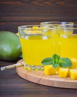 Frullato di mango con cannuccia e menta in un bicchiere di vetro. piatto con mango affettato.